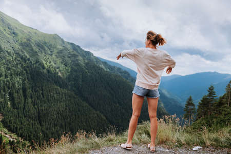 Young woman standing on cliffs edge and looking to a sky with raised hands
