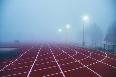 Lkw- und Feldkonzeptfoto. Rote Leichtathletikbahn im Morgennebel. Lauffoto, Standard-Bild