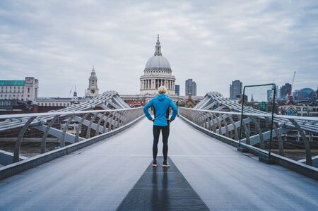 Young active man standing at Millennium Footbridge over the Thames and looking at St Paul's Cathedral.. Foto de archivo