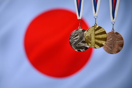 Silhouette of tree medal: Gold, Silver an Bronze. Japan flag in background..