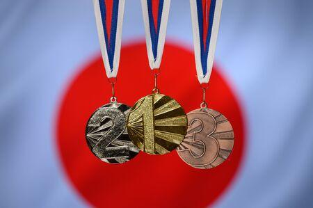 Medal set, gold silver and bronze, japan flag in background. 版權商用圖片