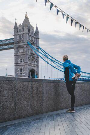 运动员在早晨在伦敦跑之前热身。塔桥梁在背景中