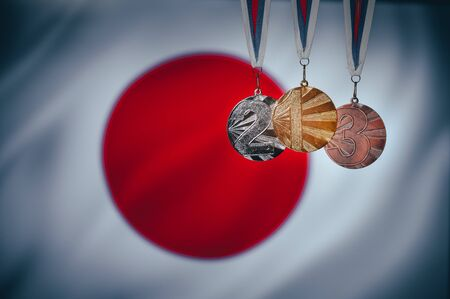 Gold silver and bronze medal for athlete, japan flag in background. 版權商用圖片