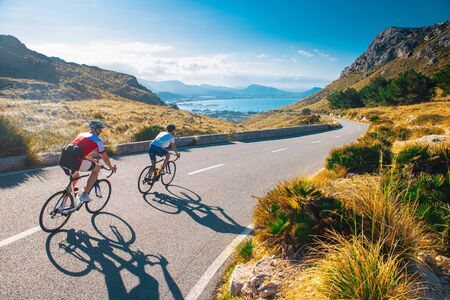 Road cycling photo. Two triathlete train in beautiful nature. Sea and mountains in background. Alcudia, Mallorca, Spain.