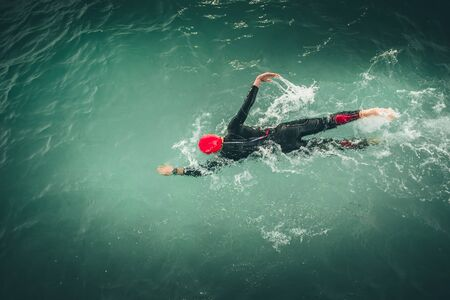 Triathlon swimmer churning up the water in the sea.. Athlete practicing for triathletic race in lak