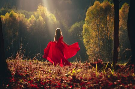 Beautiful brunette girl in a chic red dress posing in the fairy autumn forest
