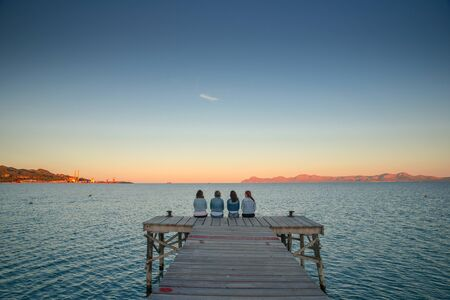 Women have rest on the pier in summer evening by the sea. Mallorca., Spain. summer vacation with friends