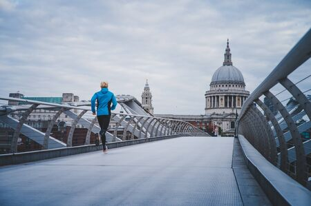 Young active man running at Millennium Footbridge over the Thames, St Paul's Cathedral in background.