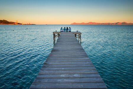 Women resting by the sea. Sitting together on the pier.. Summer sunset Stok Fotoğraf