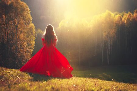 Beautiful young girl in a red dress in Fantastic autumn nature