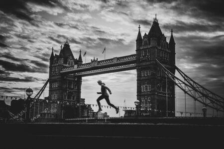 赛跑者和塔桥梁剪影在伦敦。在伦敦作为伦敦马拉松的跑的竞争的概念照片。