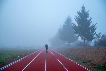 Professional athlete train at athletics running track in morning blue mist. Sport photo,