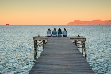 Women sitting on the pier and talk together. Mallorca., Spain. summer vacation with friends Stok Fotoğraf