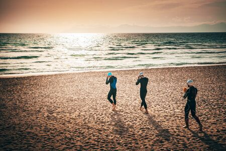 Three triathlon participants walking. on the beach before swimming training. Mallorca, Spain Фото со стока