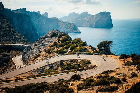 Road bikers on the road on Balearic Islands .Sea in Background. Cap de Formentor. Mallorca, Majorca, Spain