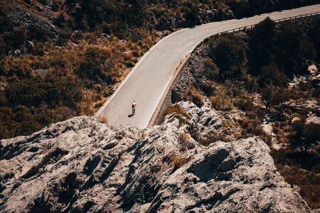 Man on road bike ride downhill on Sa Calobra, Mallorca Spain.