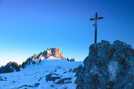 Cross on the rock in white winter nature under blue sky. Christianity photo, blue edit space Stock fotó
