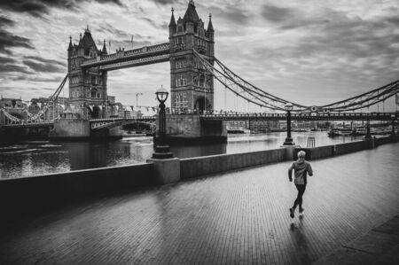 伦敦生活方式的男人在塔桥附近跑步。男跑步者在城市慢跑训练。英国伦敦塔桥附近快乐的健身男子。