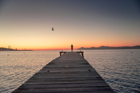 Woman standing alone on the pier.