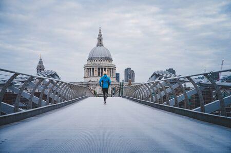 在伦敦跑,早上在泰晤士河上映了千年行人桥。圣保罗的大教堂在背景中..