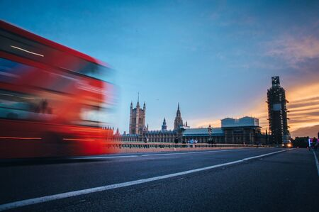 Iconic red double decker on Westminster Bridge front of House of parliament and Big Ben in London.