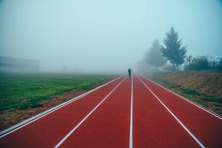 Running track over blue misty sky. Morning run