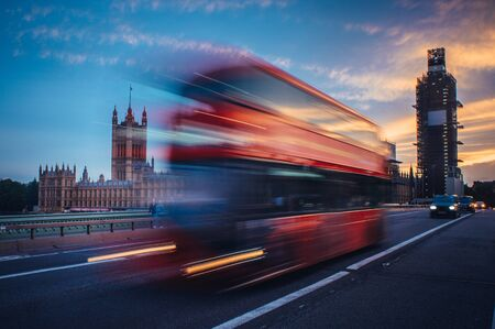 London. Classic red double decker bus crossing Westminster Bridge at sunset..