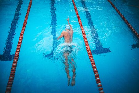 Fit swimmer training in the swimming pool. Professional male swimme.r inside swimming pool. Stock Photo