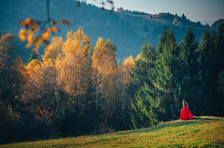 Women in beautiful red dress standing in colorful autumn nature..