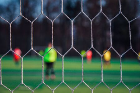 Goalkeeper in football post. Soccer net, blurred background