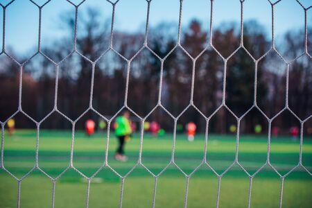 Football match behind soccer net, sport photo 版權商用圖片