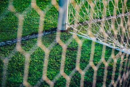 White soccer net, green grass in background, football background photo