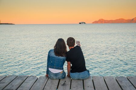 Couple in love sitting together on the pier by the sea.. Colorful sunset landscape around