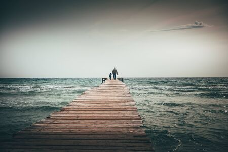 Father and son together by the sea. Family walking on the pier..