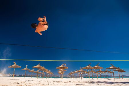 Man jumping on slackline on the summer tropical beach. White sand and blue sky in background slack line photo, edit space. Holiday in Mallorca, Spain. Standard-Bild