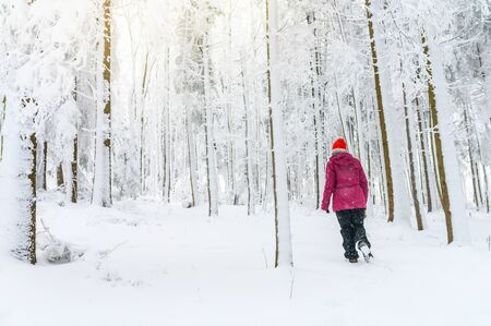 Active woman hiking in white winter snowy forest. Standard-Bild - 140648628
