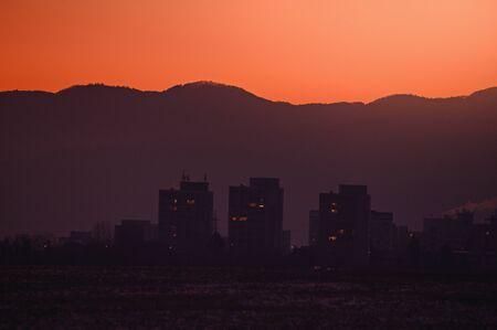 Block of flats silhouette in orange sunrise light. City in the morning