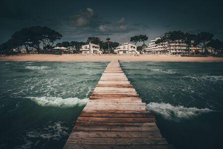Wooden pier in the sea in summer holiday resort. Mallorca, Spain 版權商用圖片