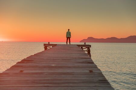 Man standing alone on the pier. Summer sunset sky in background.. Foto de archivo - 140648845
