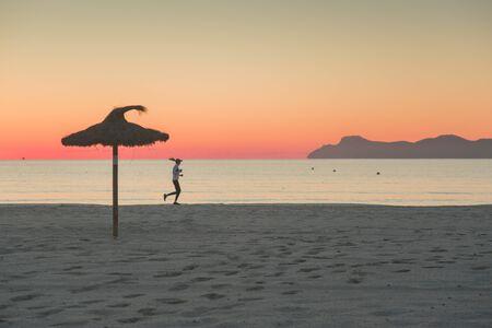 Female runner silhouette on morning beach in summer sunrise light.. Sport photo, running exercise, motivation, warm up. 免版税图像