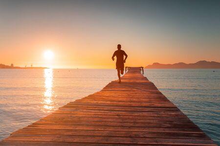 Morning Training. Runner train in beautiful sunrise light. Sport photo.. Playa de Muro