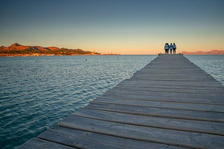 Women standing together on the pier in sunset light. 免版税图像