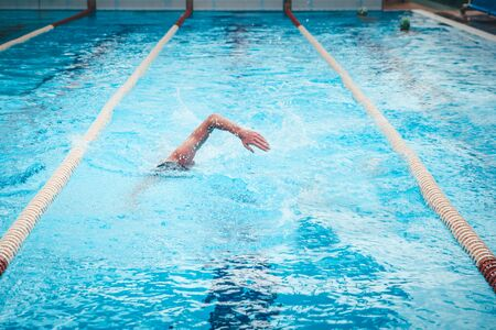 Fit swimmer training in the swimming pool. Professional male swimme.r inside swimming pool. Reklamní fotografie