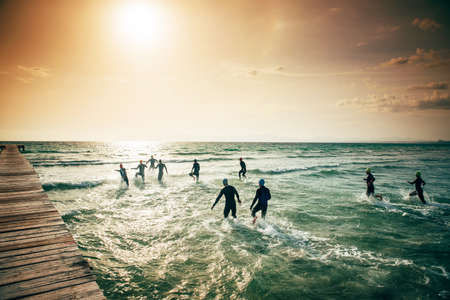 Competitors in wet suits running into the water. at the start of a triathlon. Sea in Mallorca, sunset light in background