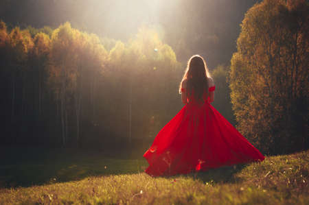 Incredible, amazing, seductive girl, in a red dress. The background is fantastic autum Stock Photo