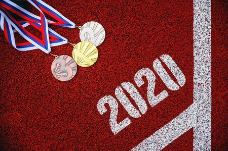 Ensemble de médailles sur piste d'athlétisme rouge, arrière-plan sportif pour l'année 2020. Événement multisports Banque d'images