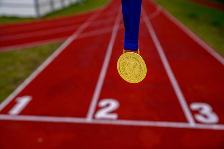 Sport inspiration, concept photo, Gold medal, red running track in background, sport motivation concept photo