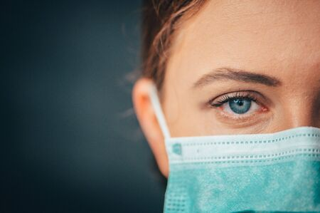 Close up portrait photo, Eye of Yong Female Doctor. Protection against contagious disease, coronavirus, hygienic face surgical medical mask to prevent infection. Black background
