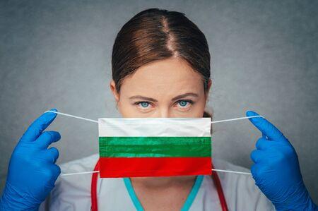 Coronavirus in Bulgaria Female Doctor Portrait hold protect Face surgical medical mask with Bulgaria National Flag. Illness, Virus Covid-19 in Bulgaria, concept photo Standard-Bild