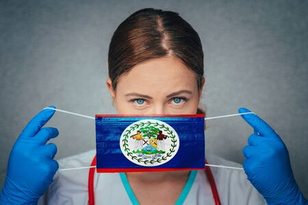 Coronavirus in Belize Female Doctor Portrait hold protect Face surgical medical mask with Belize National Flag. Illness, Virus Covid-19 in Belize, concept photo Stock fotó